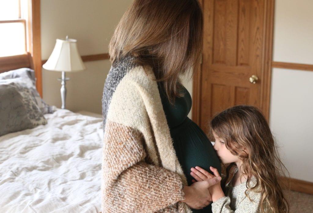 girl kissing pregnant belly