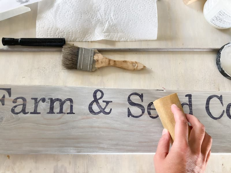 I went over the whole thing with a bit of sandpaper to distress it a bit and make it look old.  I didn't want the letters to be so bold and black.  After sanding,  go over it again with a bit of liming wax or glaze.